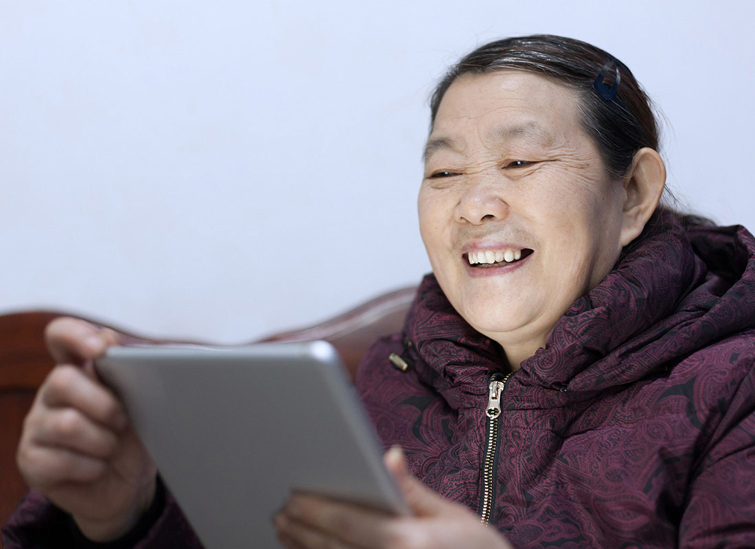 A woman is visibly enjoying using her tablet