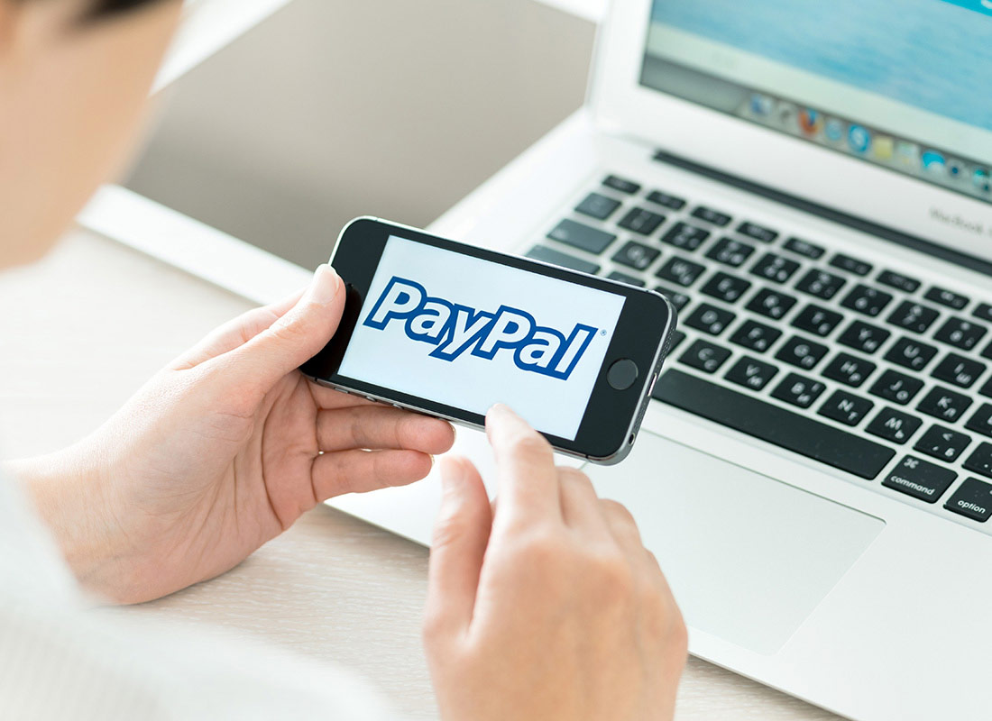 Shows a website being viewed on a laptop while a mobile phone is being used to look at PayPal