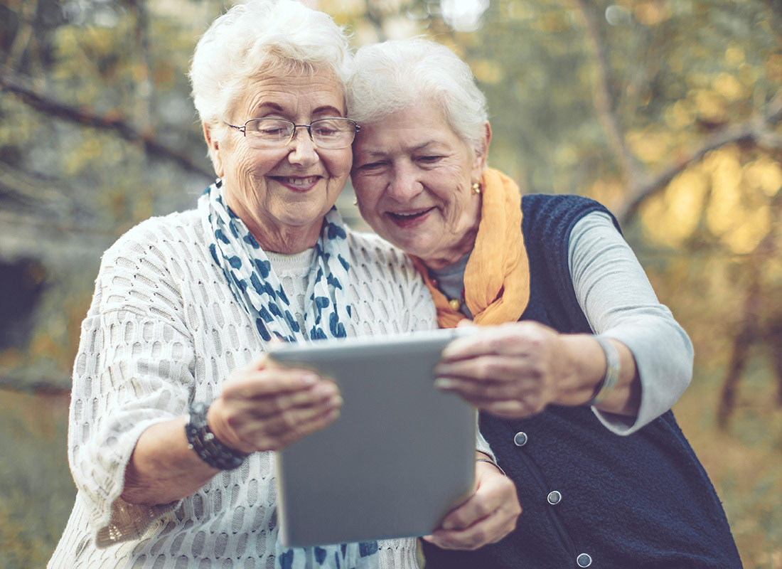 Two ladies take a photo of themselves with their tablet while they are out for a walk