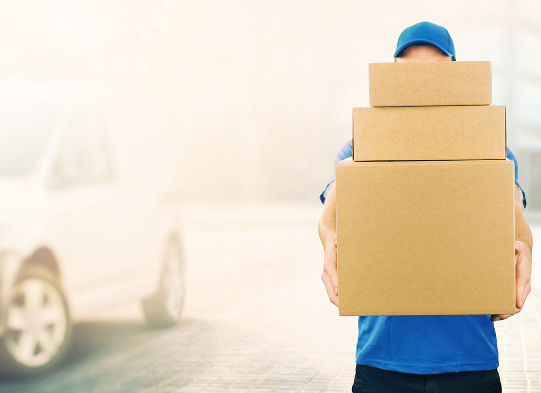 A delivery man holding multiple parcels