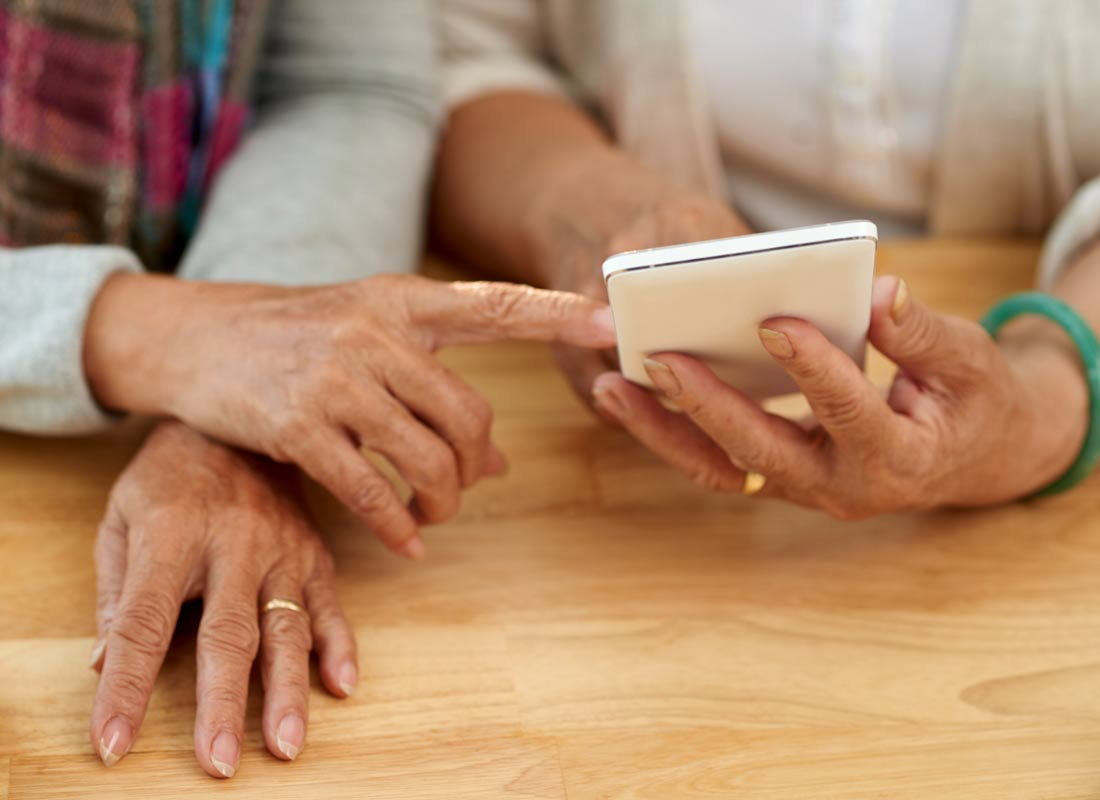 Two woman share some memories with the help of their smartphone