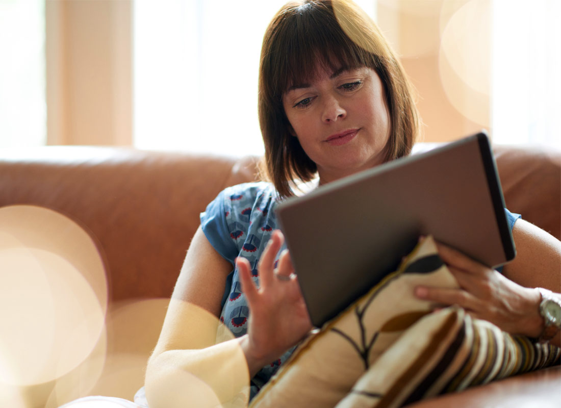 Woman comfortably relaxes with her tablet on the lounge