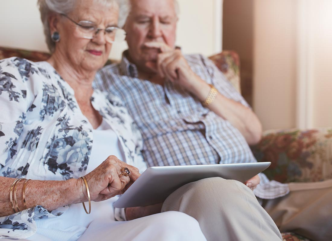 A couple look through photos from their last family gathering with the help of their tablet
