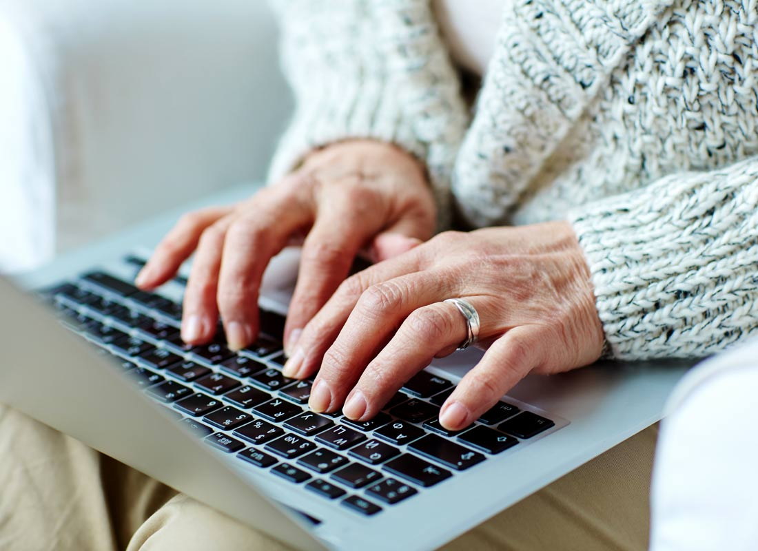 A woman's hands typing on a laptop