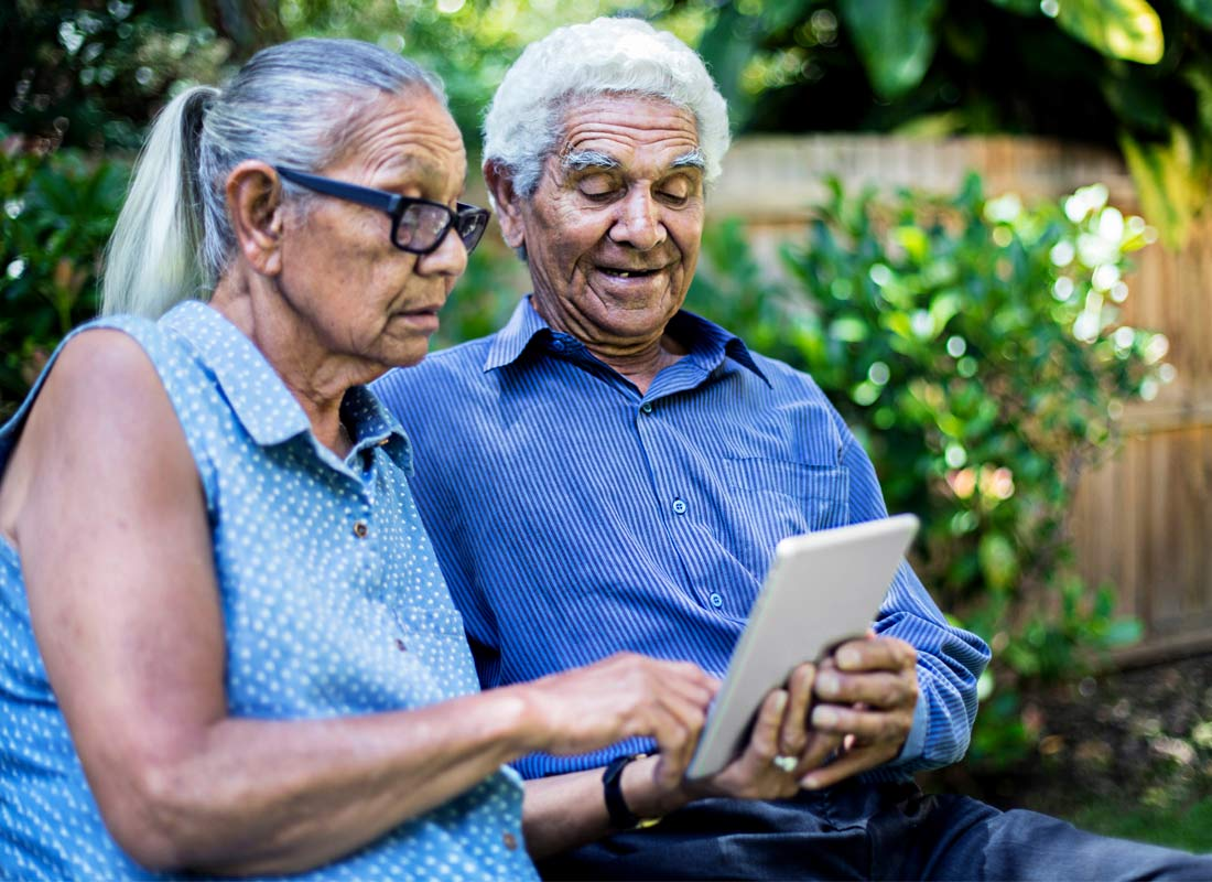 A couple enjoy interacting with their tablet while out in the garden