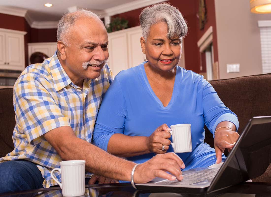 A couple look at their computer screen while enjoying a cup of tea at home