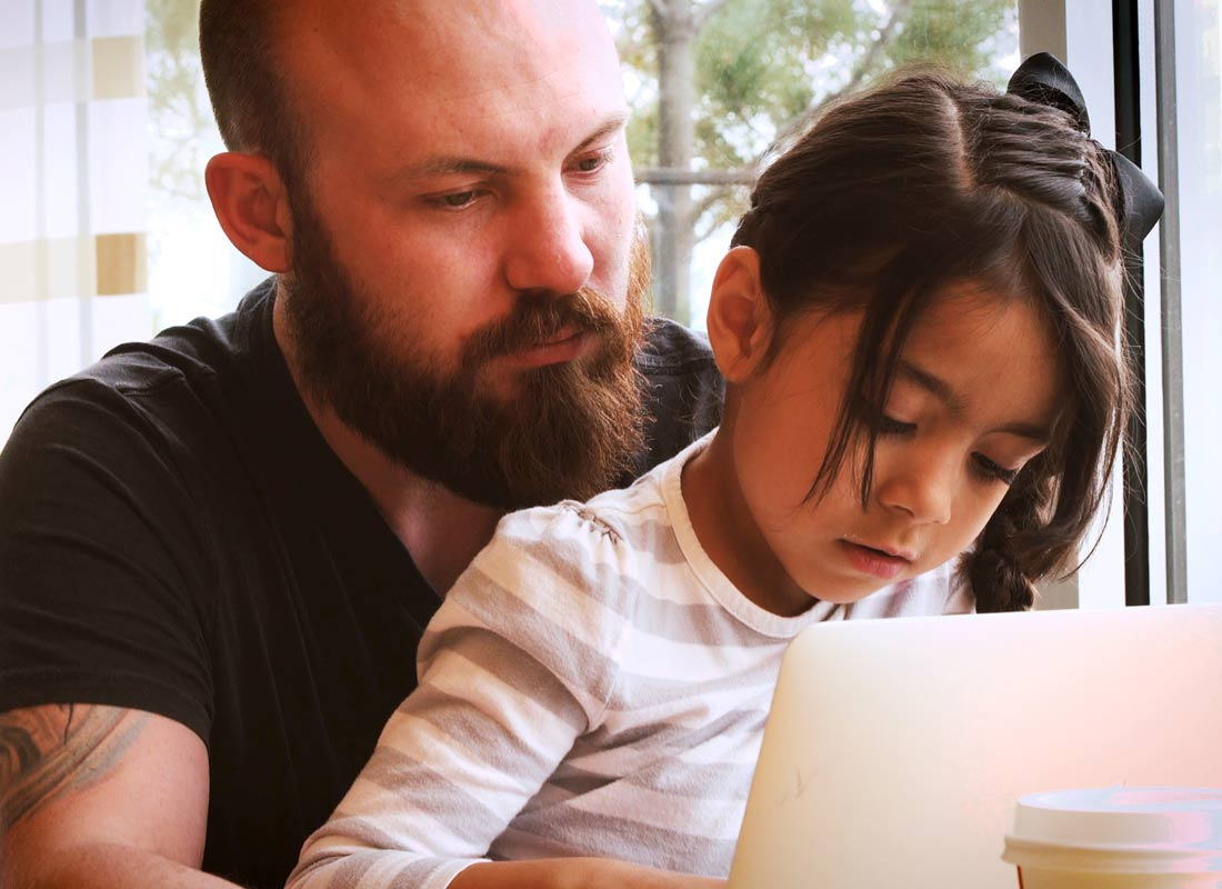 a dad and daughter using a touchscreen together