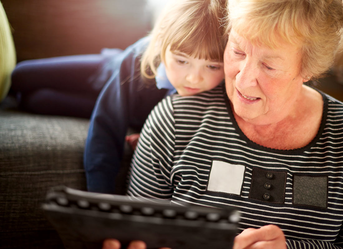 a grandmother showing her granddaughter some pictures on her touchscreen device