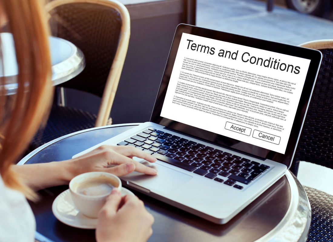 A woman sits at a cafe table drinking a coffee with her laptop open to a Terms and Conditions page of a website