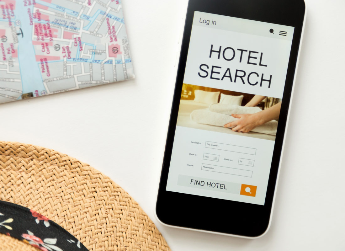 Holiday preparation is happening with a map, a hat and a hotel search on a mobile phone