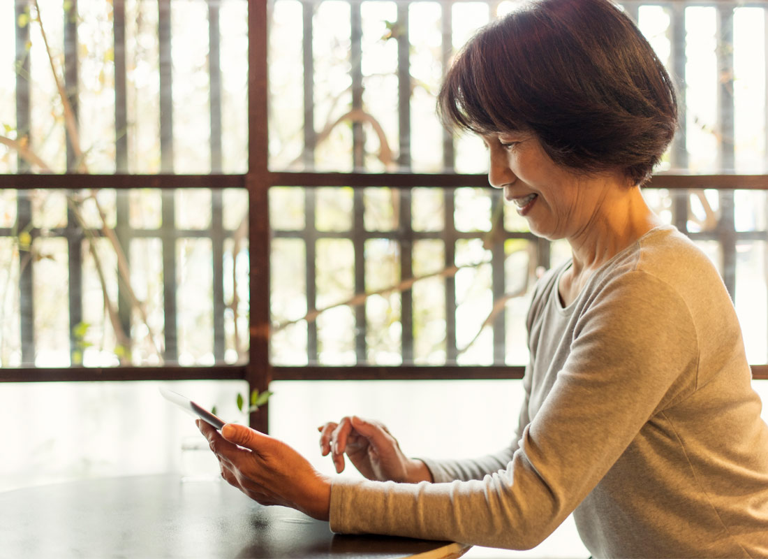 A woman happily looks at her mobile phone
