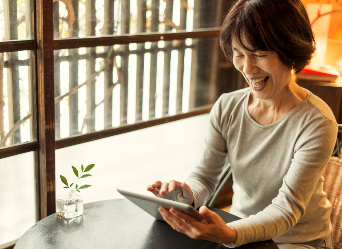 A woman is visibly happy and enjoying what she is looking at on her tablet