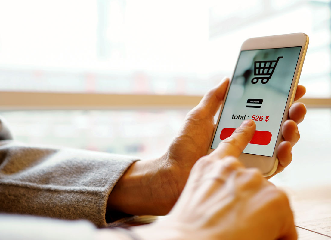 Someone pressing the final button to make their online purchase on their smartphone