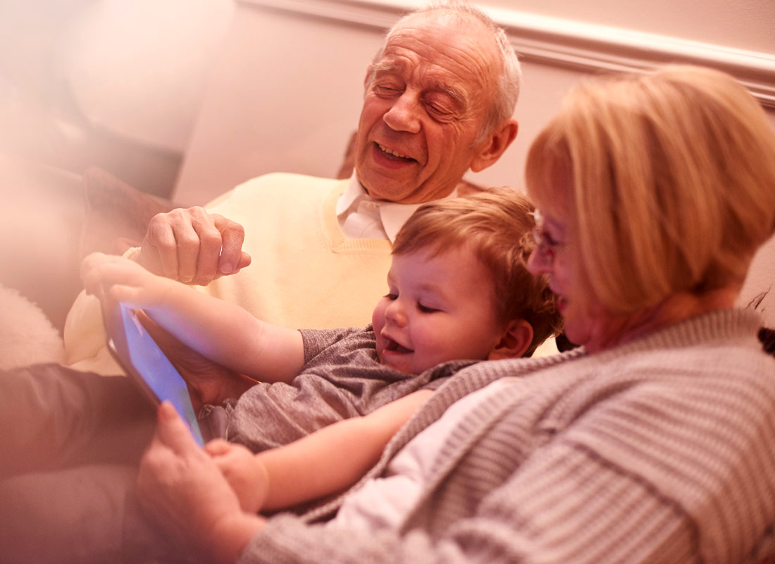 Grandparents and grandchild all sit together enjoying what they are watching on their tablet