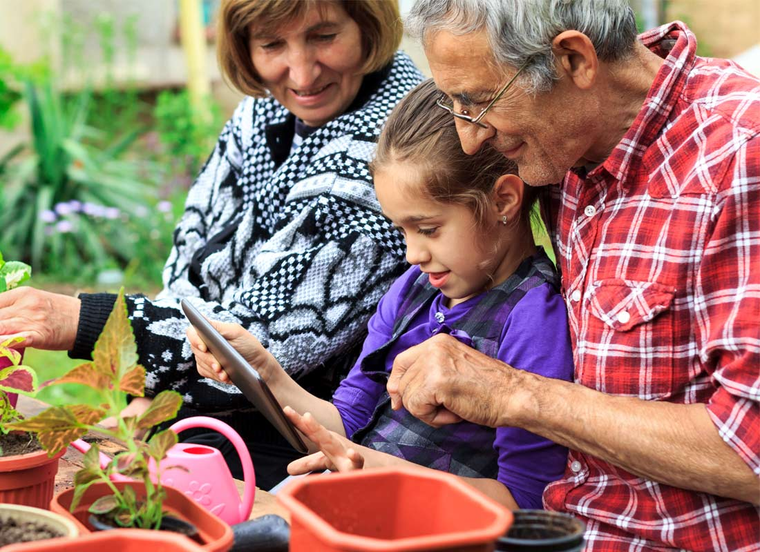 Grandparents enjoy some time in the garden using a tablet with their granddaughter