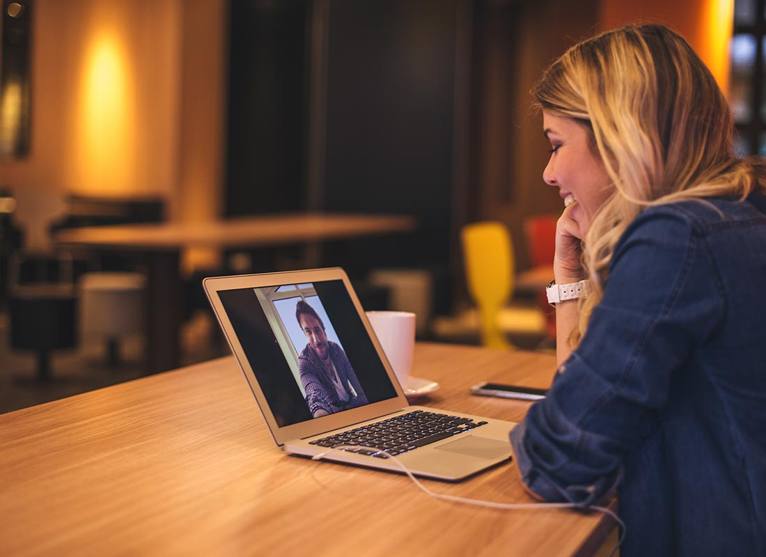 Two people video chatting on a laptop