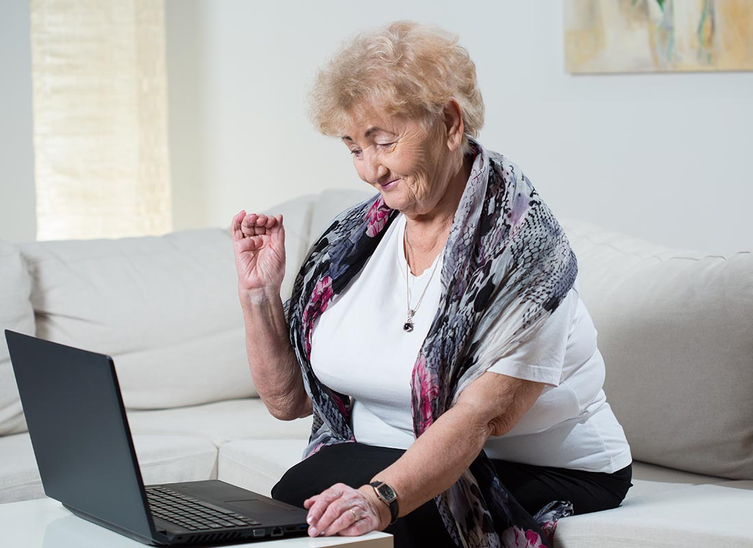 A lady using her laptop to Skype with the family