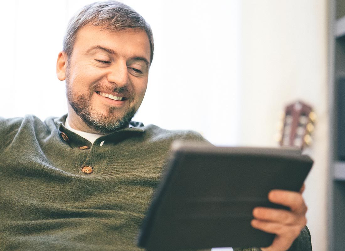 A man relaxing at home using his tablet to Skype his friends
