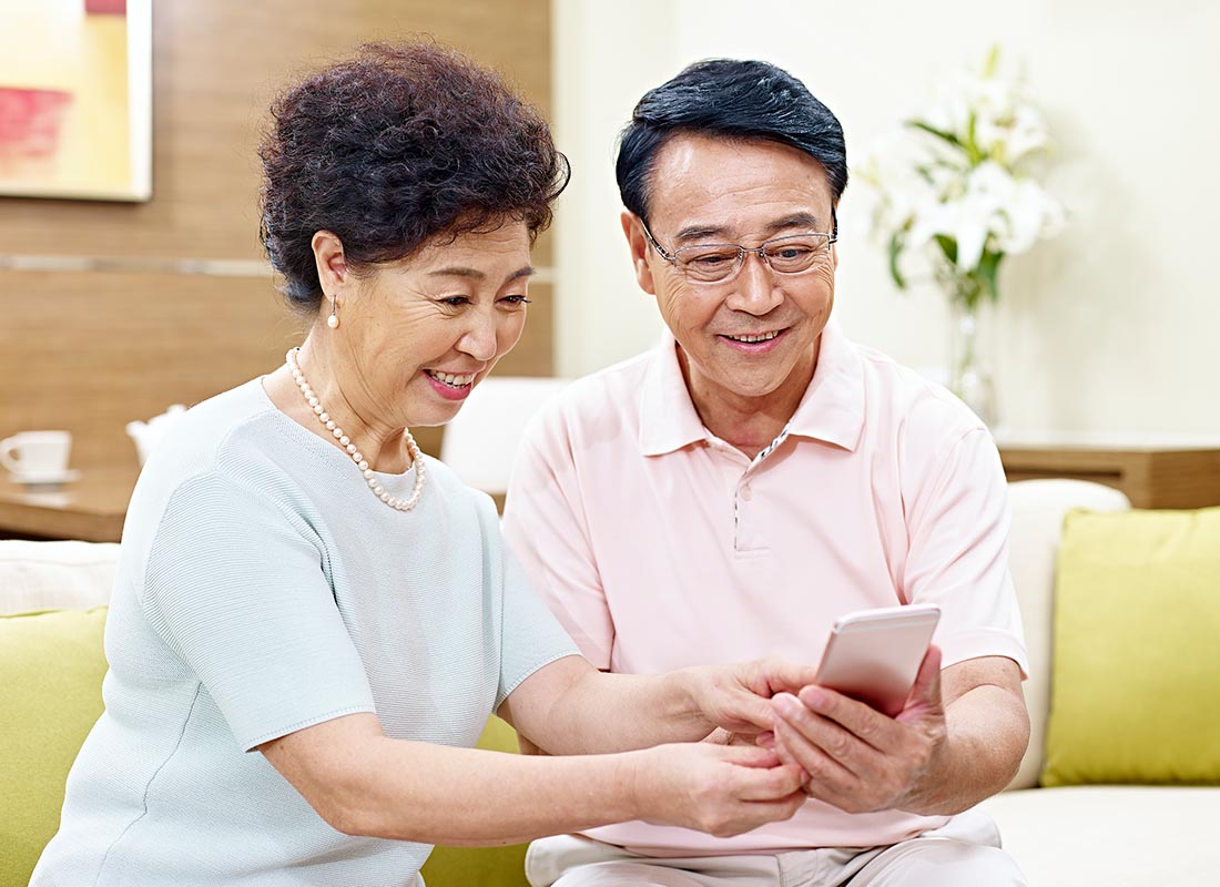 A couple saying hello to their family using a mobile device