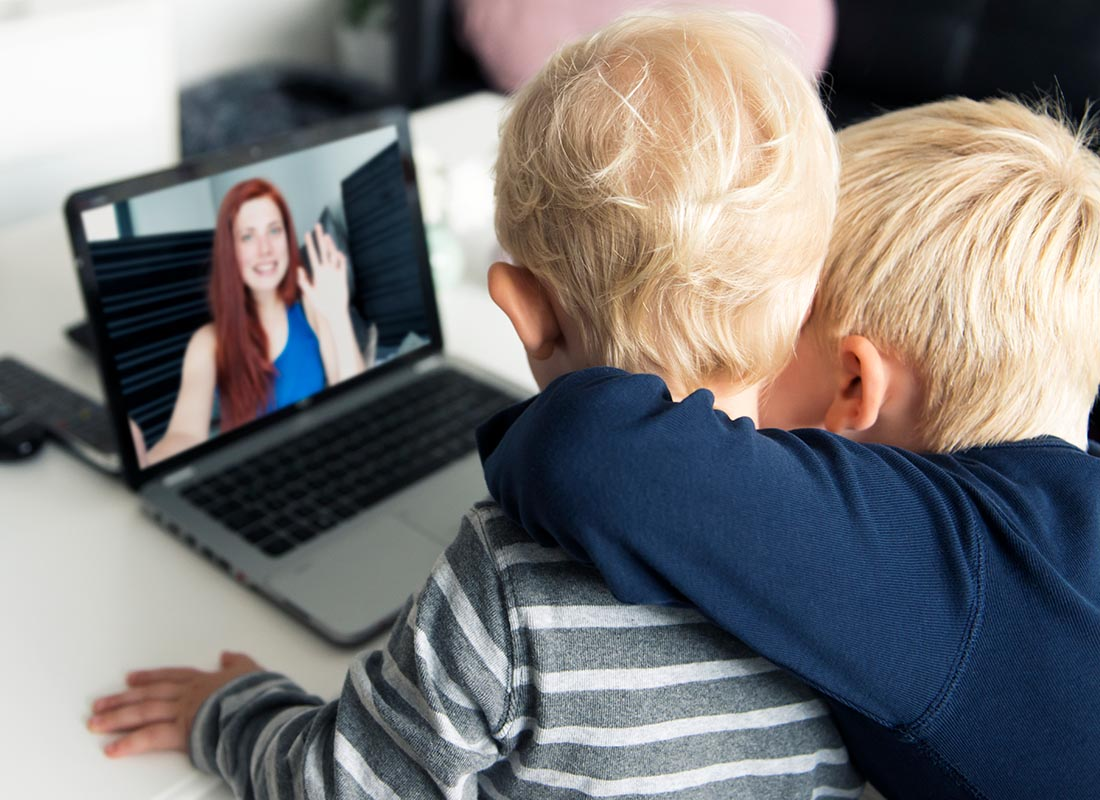 Two children saying hi to their mum over the internet