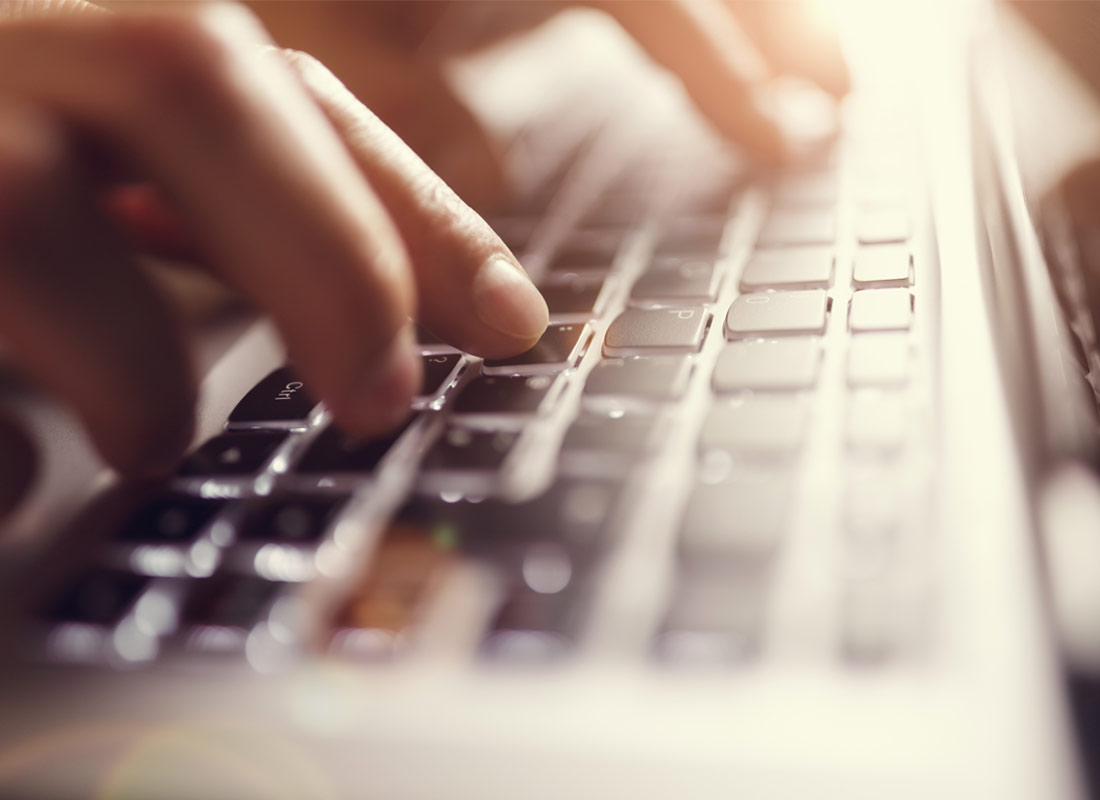 A close up of hands typing on a keyboard