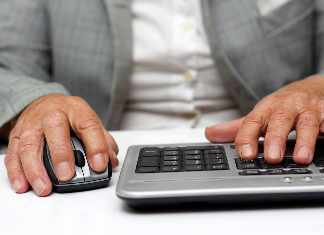 A close up of hands on a mouse and keyboard