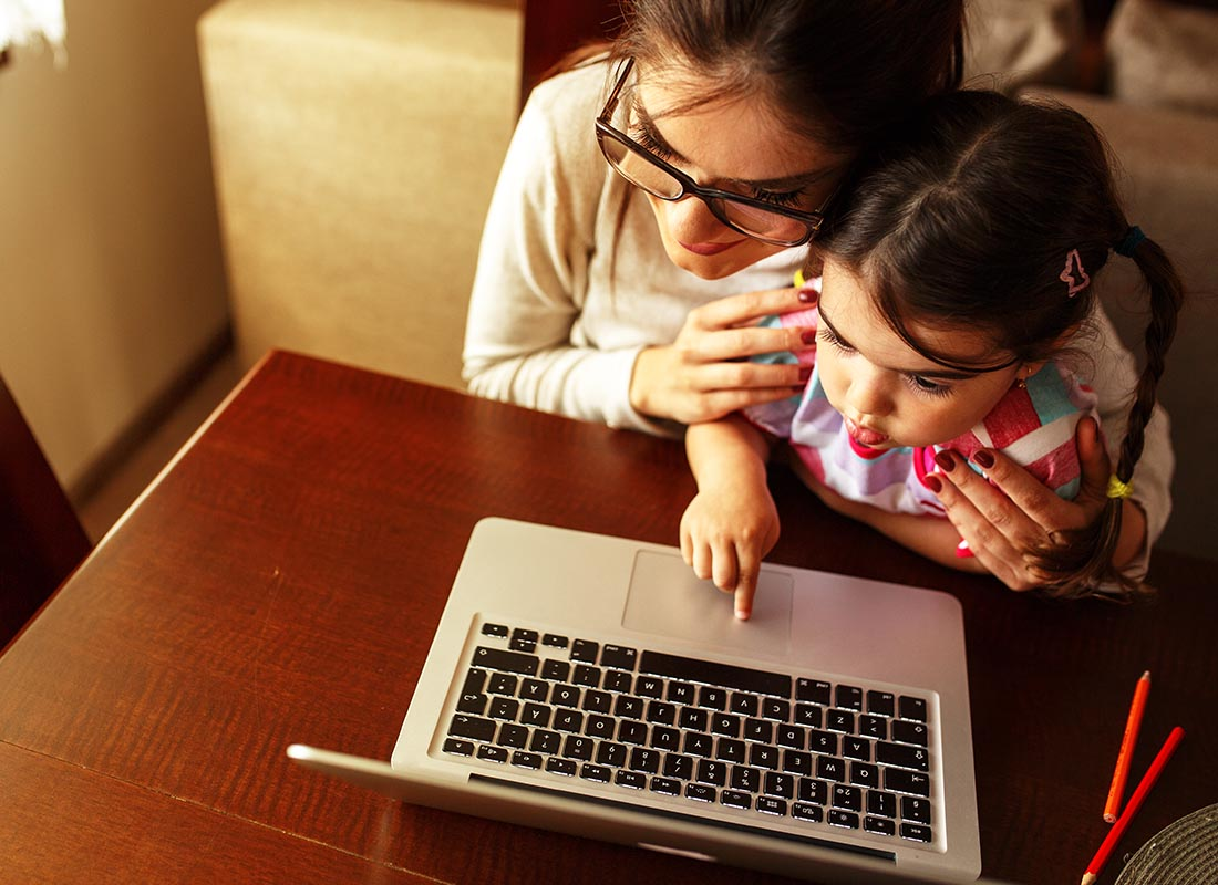A mother and daughter using their laptop to research the internet
