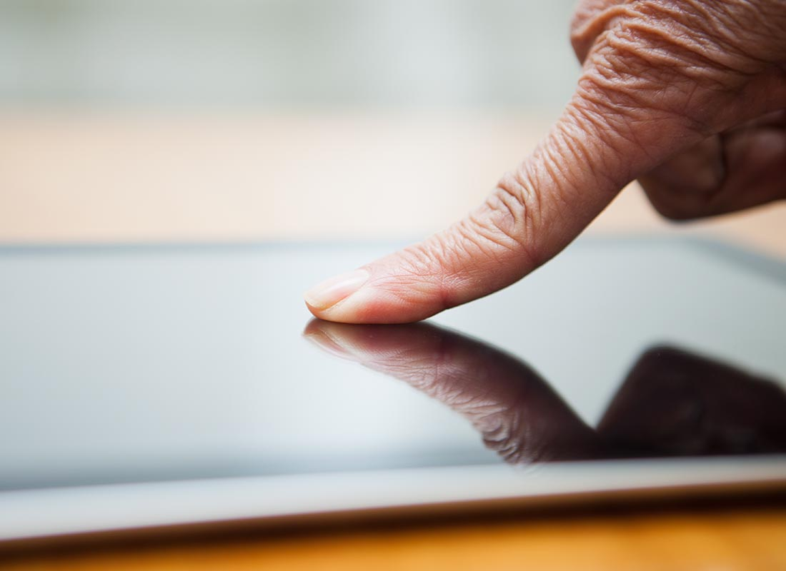 A close up of a finger pressing the touchscreen of a tablet