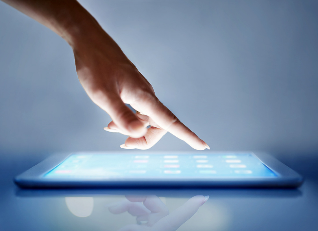 A close up of a hand using the touchscreen on a tablet computer