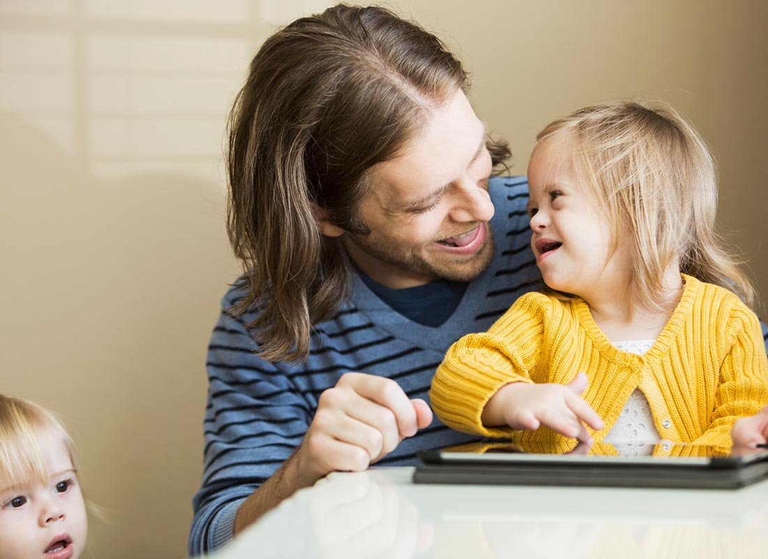 A dad and kids enjoying using their tablet together