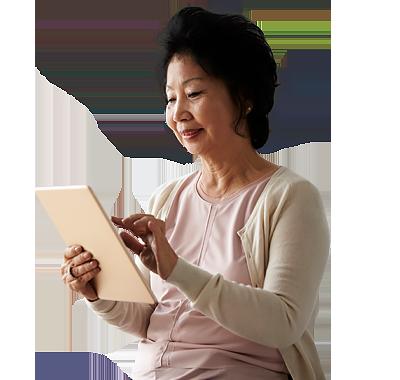 Senior Woman Sitting On Bed Using Digital Tablet.