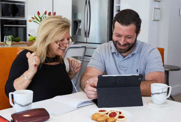 Video still image of older woman and son learning on tablet device at kitchen table