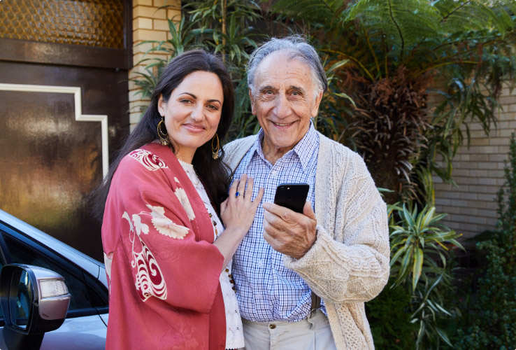 Photo of 70 year old father holding smart phone and 40 year old daughter gently embracing him.