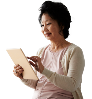 Senior Woman Sitting On Bed Using Digital Tablet.