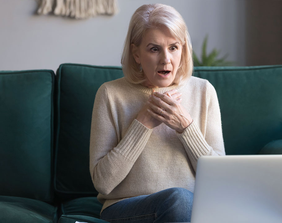 Older woman sitting on green couch with laptop looking shocked.