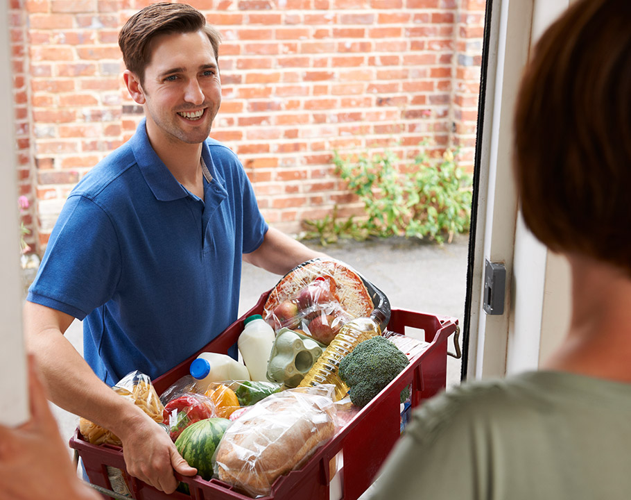 A young man delivers fresh groceries to the home of an older female.