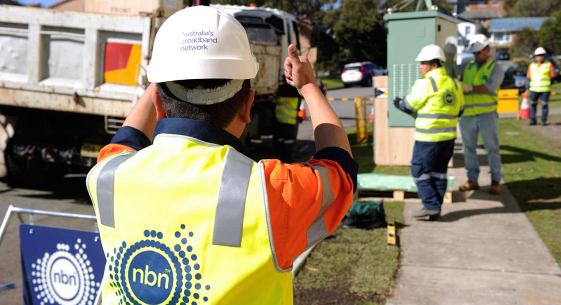 Workers installing NBN infrastructure on suburban street.
