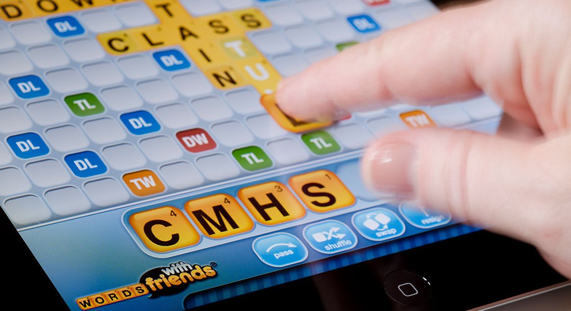 Person moving a letter into position while playing the Words with Friends game on an iPad.
