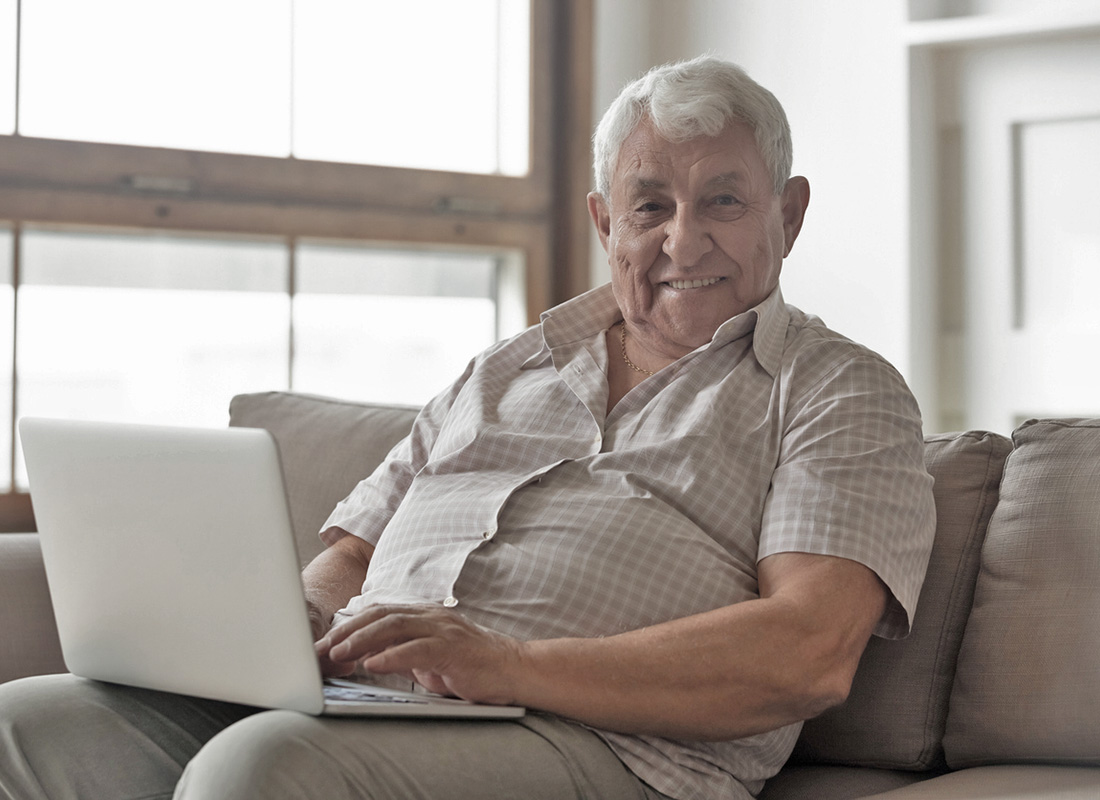 A gentleman sitting comfortably with a laptop ready to check his online bank account