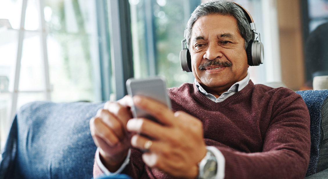 Mature man on couch listening to a podcast on his smart phone