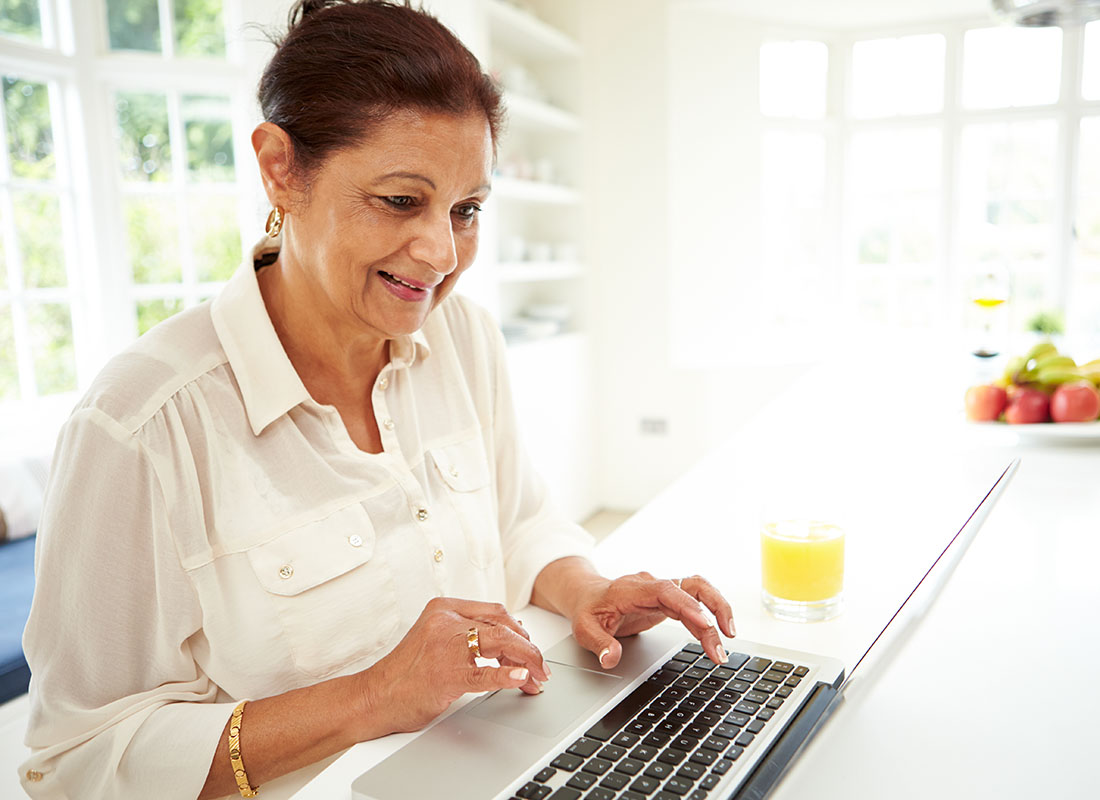 Lady working on a laptop at her kitchen table
