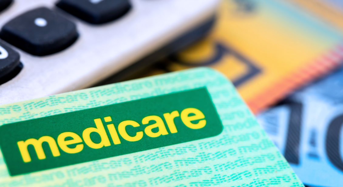 Medicare card sitting on calculator and cash.