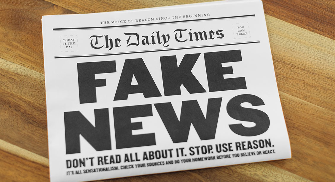 A newspaper publication with the headline Fake News sits folding on a kitchen table.