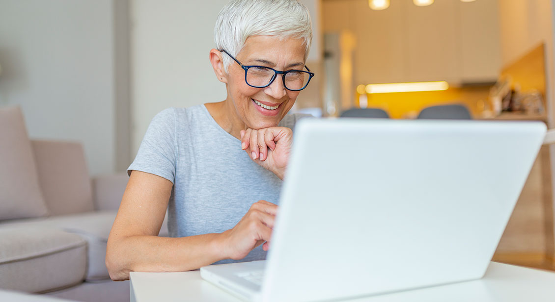 Close-up portrait of casual 60year old woman using her laptop while sitting on couch.