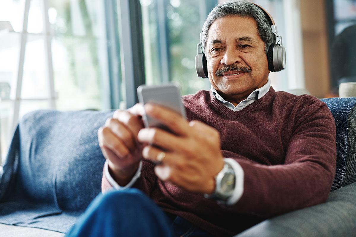 man sitting onlounge using smart phone