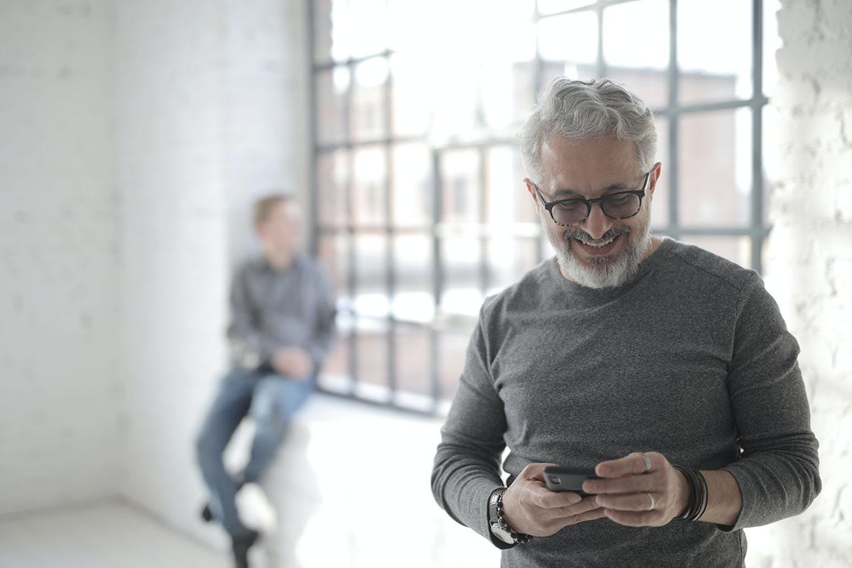 Man smiling holding smart phone
