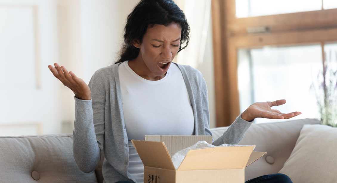 A young brown skinned woman sitting down appears disappointed after opening her parcel.