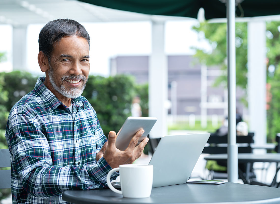 A gentleman stays in touch with loved ones via social media on his laptop and tablet.
