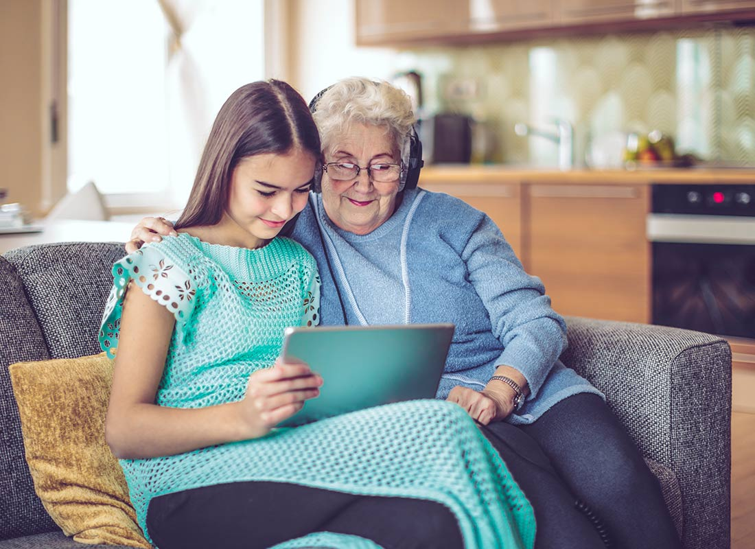 A granddaughter and grandmother enjoying time together with their tablet