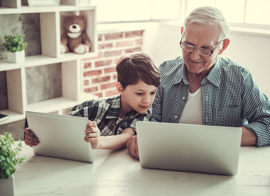A grandfather and child sharing a tablet and laptop computer together